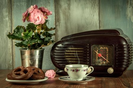 antique radio, pink flowers, pretzels, and tea cup on a wooden table with blue worn wood backdrop