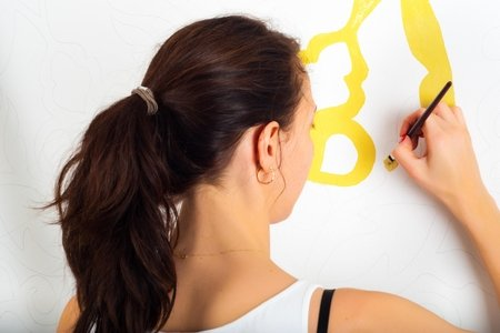 woman painting pattern on white wall with yellow paint
