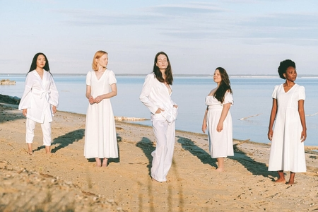 five women in all white standing on the beach