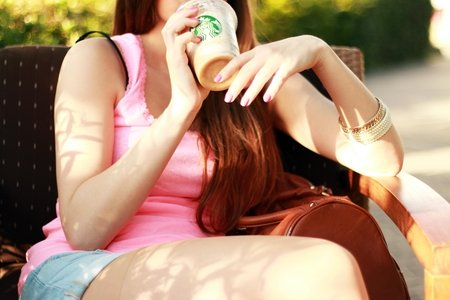 Woman in Pink Tank Top Sitting on Chair While Drinking on Starbucks Cup