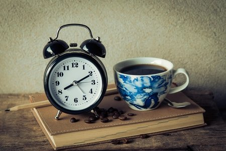 coffee in a blue pattern mug next to an analog alarm clock
