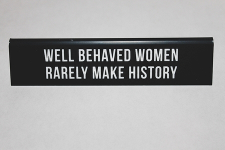 "black placard stating on ""WELL BEHAVED WOMEN RARELY MAKE HISTORY"" on white table"