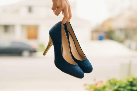low-depth of field photo of person holding navy stilletos