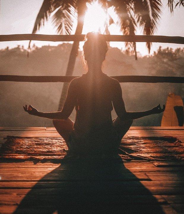 girl meditating at sunset