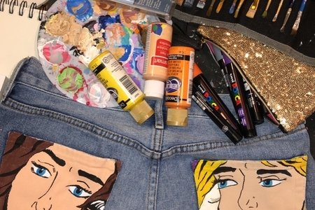 Painted jeans with paint bottles and brushes around them