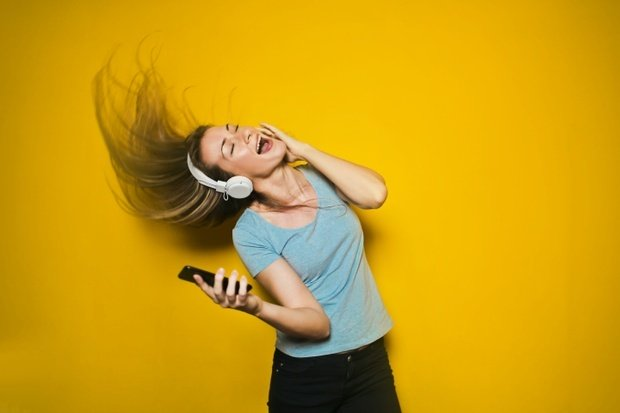 Woman wearing white headphones and dancing