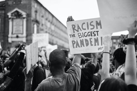 "person holding a sign that says ""racism is the biggest pandemic"""