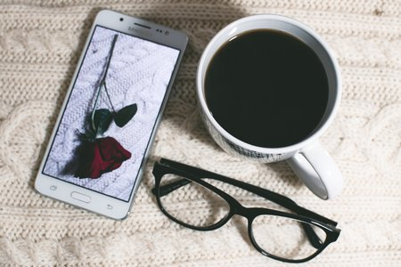 Samsung phone with a rose picture, glasses, mug of coffee on a white textured background