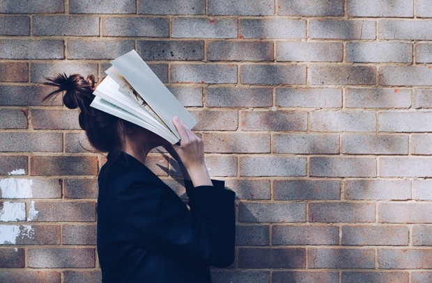 Girl covering face with book