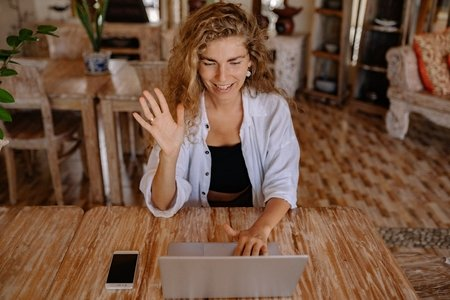 Woman with curly hair waving and saying hi to someone through her laptop.