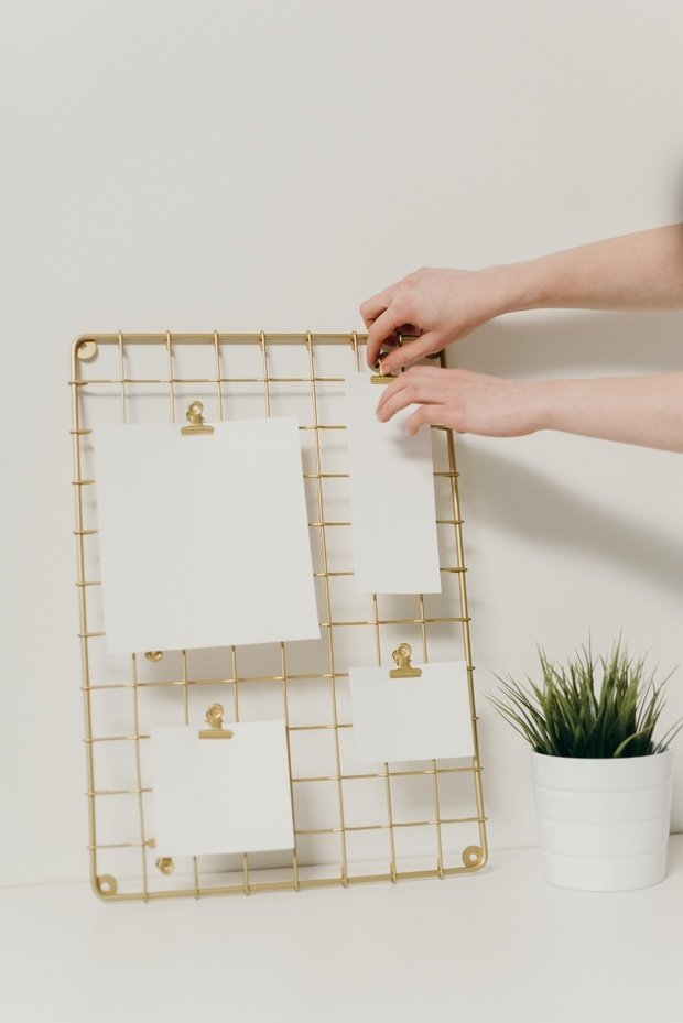 person holding white paper and hanging it on gold standing rack
