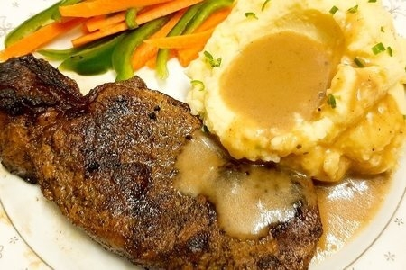 plate of mashed potatoes with gravy, vegetables, and steak