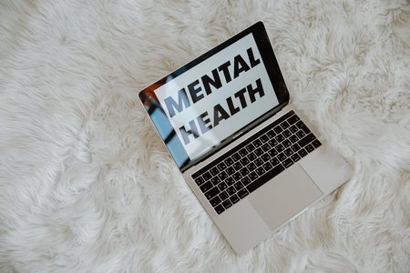 "Laptop with text on the screen that reads ""Mental Health"" on a white carpet"