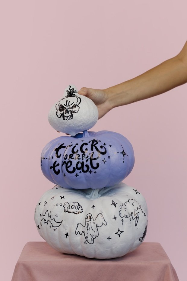three painted pumpkins stacked on each other