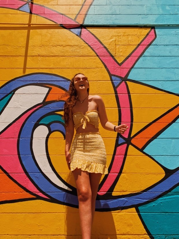 Becca McCandless wearing yellow dress in front of colorful sun wall