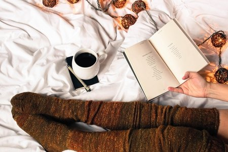 Mug of black coffee next to woman reading a book