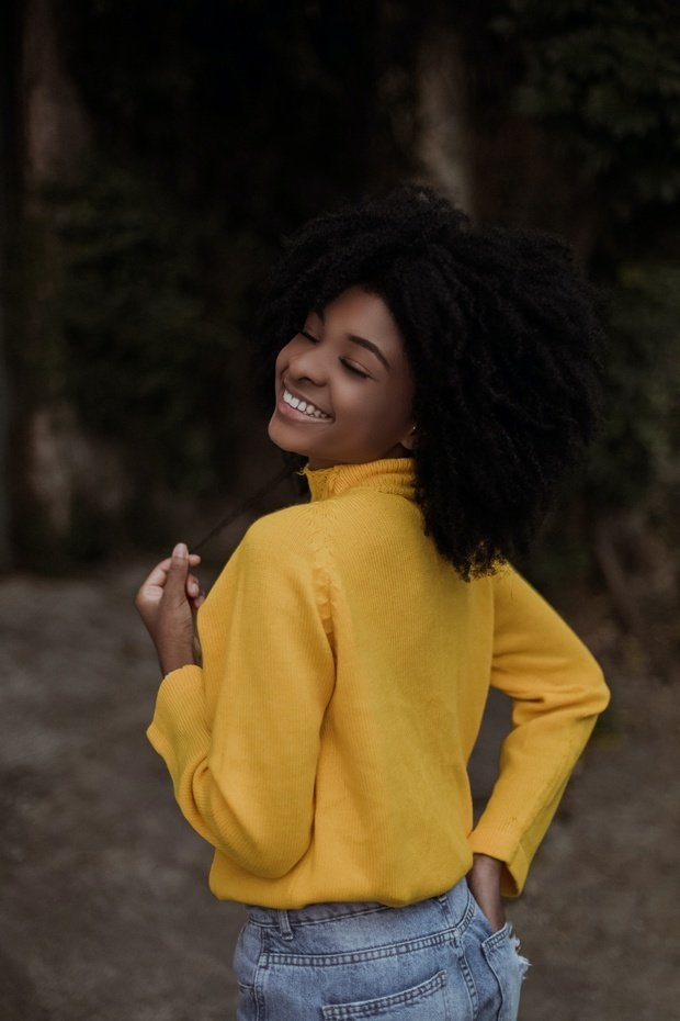 young woman smiling in yellow sweater