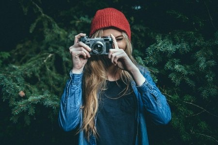 blonde woman holding camera outside
