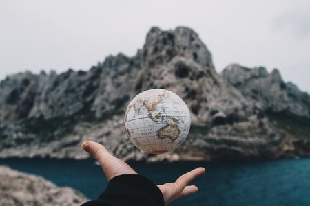 person holding small globe