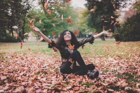 Woman sitting in leaves during fall time