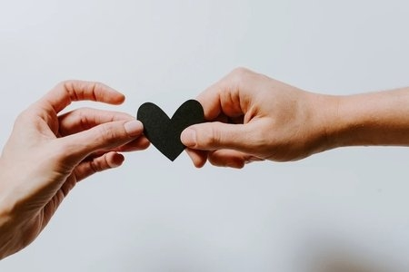 people exchanging a paper heart