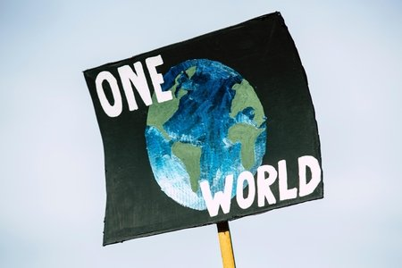 "sign that has the earth on it that says ""one world"""