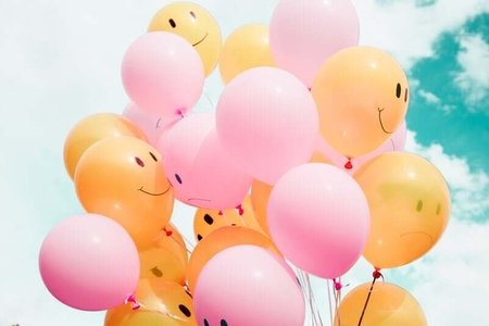 multiple yellow and pink balloons, some with smiles and frowns on them