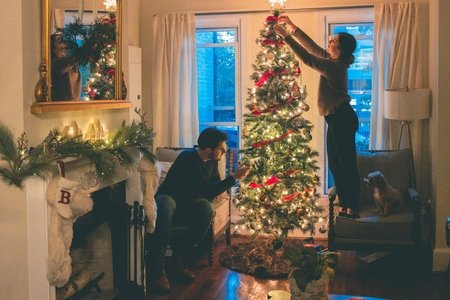 a couple decorating a Christmas tree