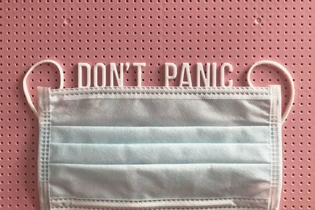 "reuseable surgical mask with phrase ""don't panic"" on a pink letter board"