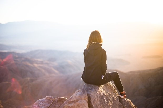 Woman sitting on top of mountain at sunrise